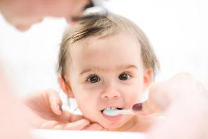 Baby getting her teeth brushed